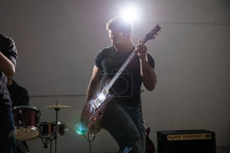 Man playing electric guitar in concert with bright light on stage
