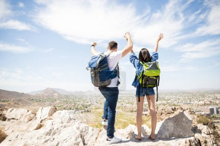 People with hands up looking at beautiful city and mountain landscape