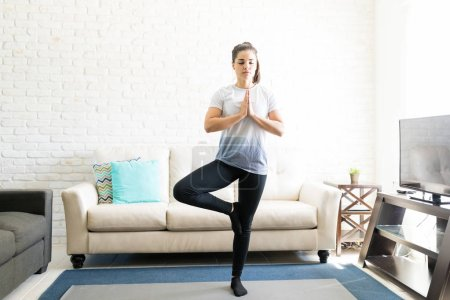 young hispanic woman practicing tree pose yoga at home