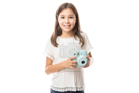 Smiling young girl holding photo camera and taking pictures isolated on white background