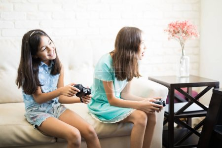 Photo for Little sisters with gamepads playing video game together while sitting on sofa at home - Royalty Free Image