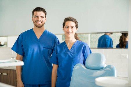 Photo pour Portrait de sourire dentistes masculins et féminins dans scrubs permanent à la clinique dentaire - image libre de droit