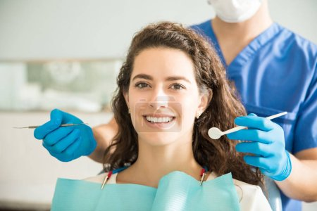 Portrait of smiling young woman with dentist holding dental tools at clinic