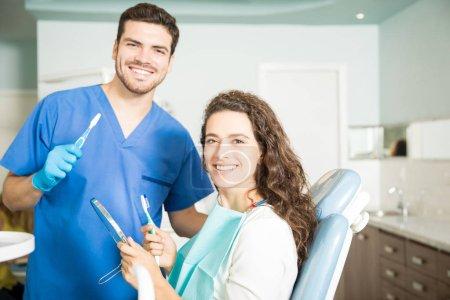 Photo pour Portrait d'un dentiste souriant et d'une femme tenant des brosses à dents et un miroir dentaire en clinique - image libre de droit