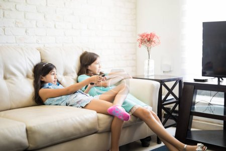 Small girl selecting tv channel with remote while sitting on couch at home