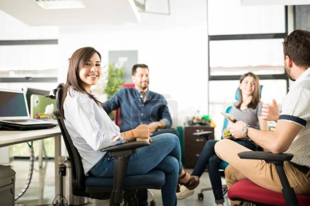 smiling young hispanic woman sitting with colleagues in meeting room