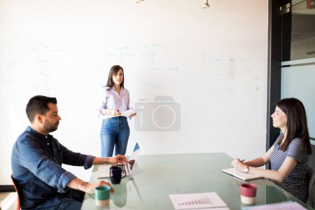 attractive latin woman giving presentation to coworkers on white board in meeting room