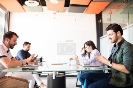 Group of business people sitting around conference table and using their mobile phones  while ignoring work and social networking.