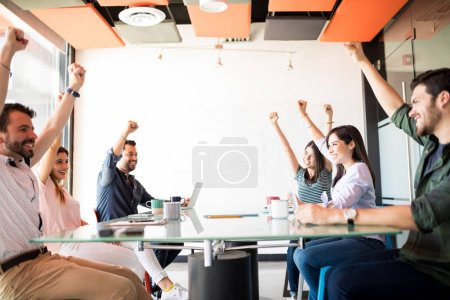 Ambitious workers keeping hands up to show their positive mood in break time in meeting room