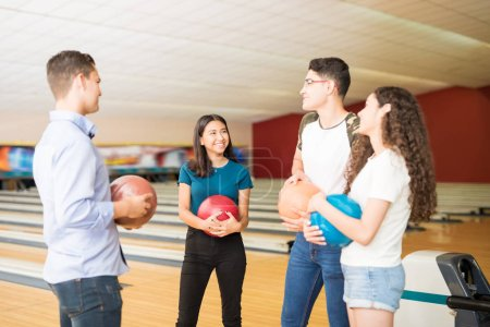 Happy teenage friends talking while having fun at bowling alley
