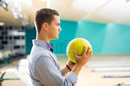 Side view of determined teenage boy holding yellow bowling ball at alley in club