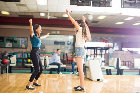 Excited teenage girls cheering while bowling in alley at club