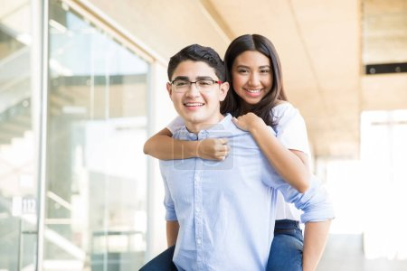 Portrait of smiling teenage boy piggybacking girlfriend in shopping mall