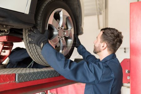 Side view of male mechanic replacing car tire at auto repair shop
