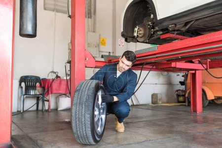 Car mechanic examining tire for replacement in auto repair shop