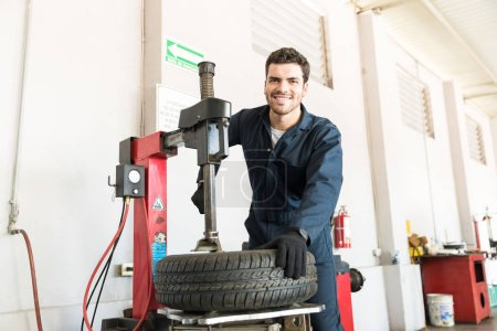 Portrait of smiling mid adult serviceman in uniform using tire changer at garage