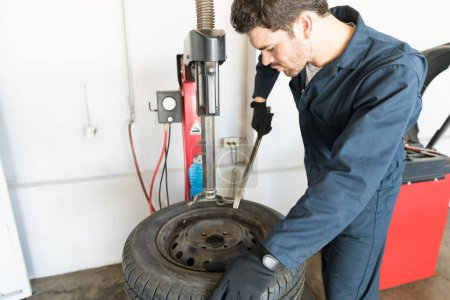 Mid adult male repairman removing tire from rim on machine at auto repair shop