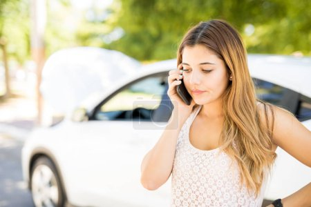 Pretty young woman calling for assistance with her car broken down by the roadside