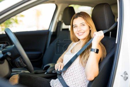 Photo pour Portrait de jolie jeune femme mettant sa ceinture sur avant de conduire immédiatement - image libre de droit