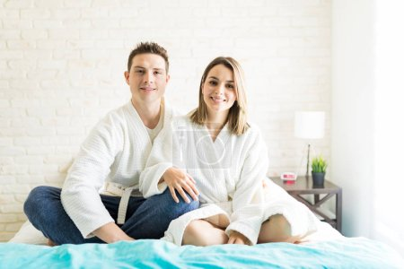 Portrait of lovely couple spending leisure time on bed at home