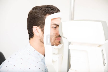 Handsome man checks his vision on the machine checking patient vision at eye clinic