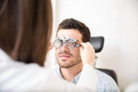 Female optician adjusting lens of trial frames on ...