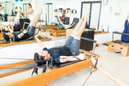 Determined young female on pilates reformer in gym