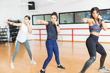 Determined women in sportswear punching the air in gym