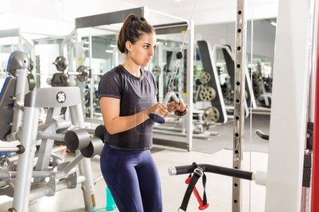 Photo for Young fit woman doing triceps extension exercise in fitness club - Royalty Free Image