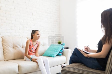 Girl sharing her problems with female psychologist sitting on sofa at home