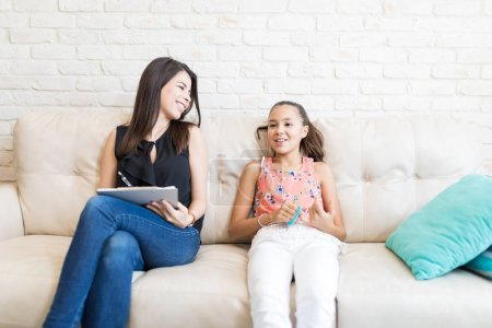 Happy psychologist looking at girl while making notes on sofa at home