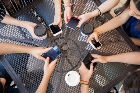 Top view of young friends hands using mobile phones at caf