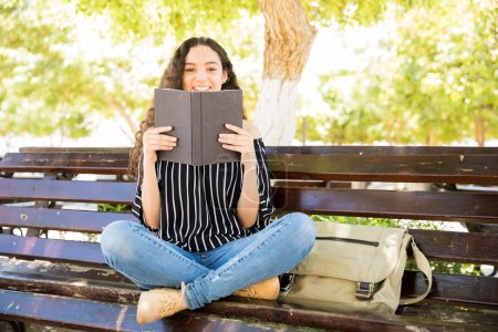 Portrait of young hispanic girl student enjoying reading a book on park bench