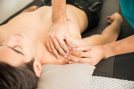 Photo pour Cropped image du thérapeute masser l'épaule de l'homme dans la clinique - image libre de droit