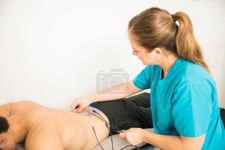 Female physical therapist positioning electrodes on customer for lower back muscle treatment in clinic