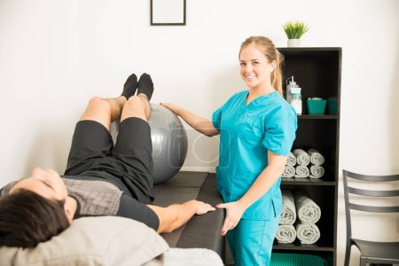 Smiling young physical therapist using exercise ball for patient's legs workout in clinic