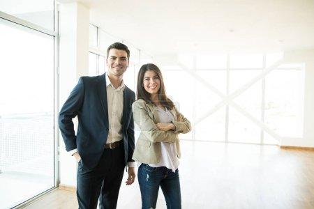 Photo pour Portrait de sourire mâles et femelles agences immobilières debout dans appartement neuf - image libre de droit