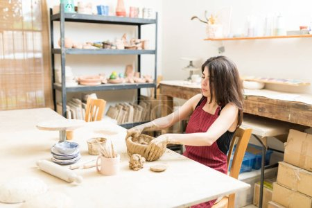 Mid adult female artisan molding clay at table in pottery workshop