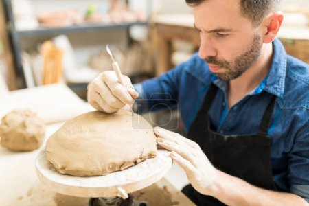 Concentrated male owner using sculpting tool on clay in pottery workshop