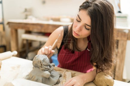 Mid adult pottery master giving clay a shape of doll in studio