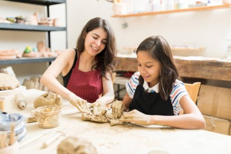 Woman and girl kneading clay to make art product at table in pottery workshop