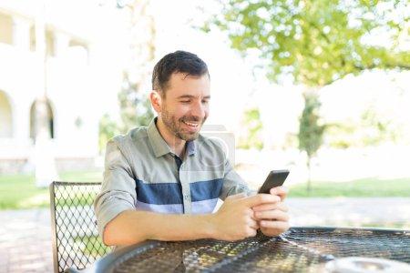 Photo pour Milieu mâle adulte, en envoyant des messages et des photos dans les réseaux sociaux à l'aide de téléphone portable à table dans le jardin - image libre de droit