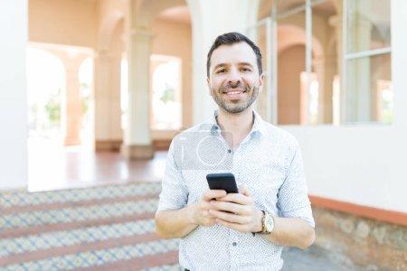 Photo pour Portrait du milieu adulte homme souriant tout en tenant le téléphone portable contre le bâtiment et multiplier - image libre de droit
