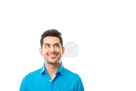 Photo for Handsome male smiling while looking at copyspace over white background - Royalty Free Image