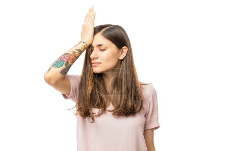 Photo for Woman realizing mistake and keeping hand on head over white background - Royalty Free Image
