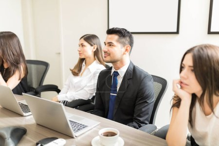 Managers from different departments discussing work in conference room at office