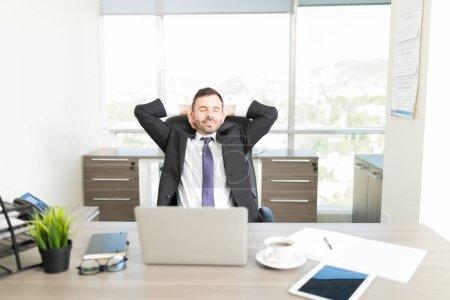 Photo pour Détendue avocat mâle avec les mains derrière la tête, assis au bureau au bureau - image libre de droit