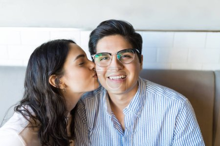 Happy young man being kissed by girlfriend on cheek while dating in coffee shop