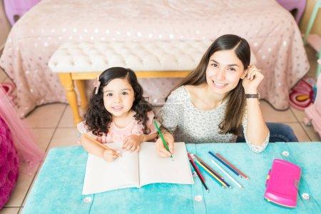 Photo pour Portrait d'un angle élevé de nounou enseignement dessin de jolie fille à table - image libre de droit