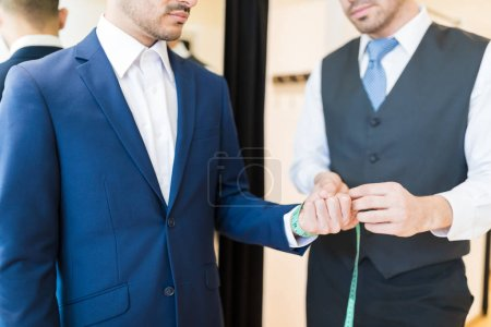 Photo for Midsection of creative young seamster measuring wrist of wealthy man in clothing store - Royalty Free Image